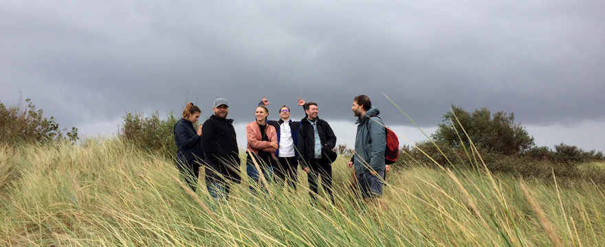 a picture of the Userlike team in the dunes – header image for blog post on company retreat